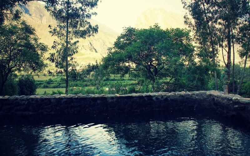 ollantaytambo_reisen_peru_heilige_tal_tour_inka_ruine_machu_picchu_steine_urubamba_berge_anden_plaza_hauptplatz_pool_mit_blick_auf_ruinen
